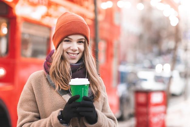 Портрет красивой девушки в теплой одежде, стоящей на улице с бумажным стаканчиком кофе на фоне боке