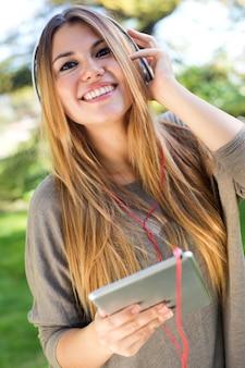 Ritratto di bella ragazza ascoltando musica con tabella digitale