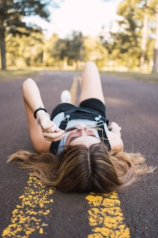 Portrait of a beautiful girl lying on the road.