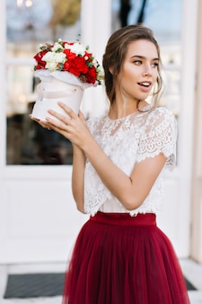 Portrait beautiful girl in marsala tulle skirt on street. she holds bouuquet of roses, looking to side