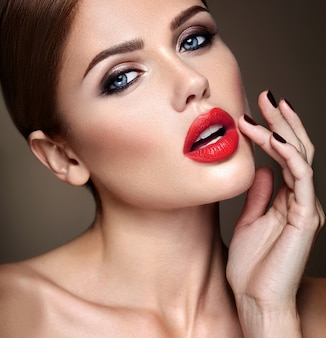 Portrait of beautiful girl model with evening makeup and romantic hairstyle. touching her red lips