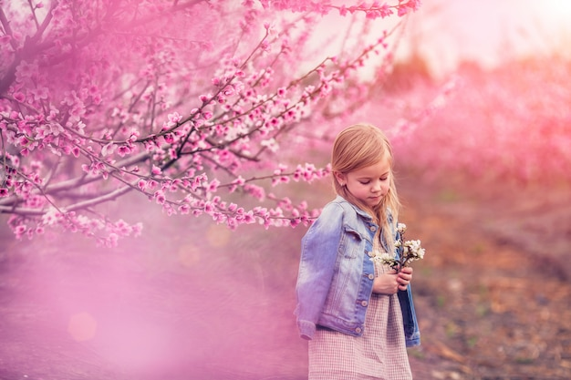 Portrait of a beautiful girl near a flowering tree of almonds and lilacs