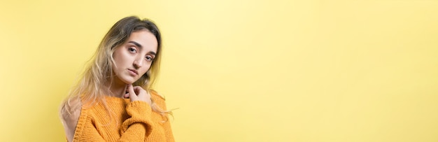 Portrait of a beautiful girl in an orange sweater looks aside with pensive expression