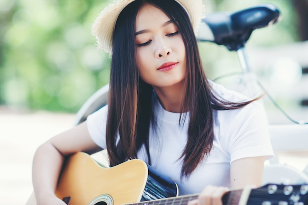 Portrait of beautiful girl playing the guitar with bike at nature