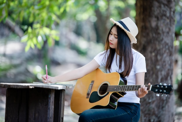 Portrait of beautiful girl playing the guitar with writing at nature
