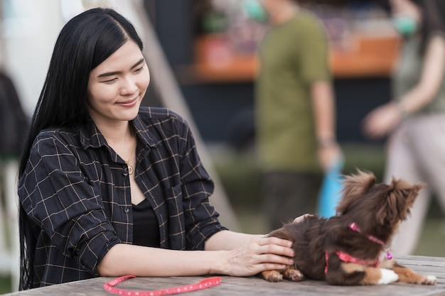 Portrait of a beautiful girl playing with her lovely puppy at outdoor in the public park. little dog with owner spend a day at the park playing and having fun. pet love stock photo
