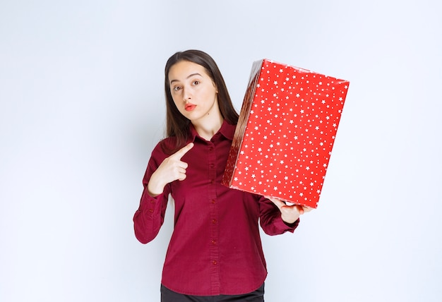 Portrait of a beautiful girl pointing at a present box over white wall .