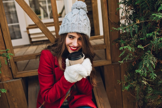 Portrait beautiful girl in red coat, knitted hat and white gloves sitting on wooden stairs  outdoor. she holds coffee to go and smiling to side.