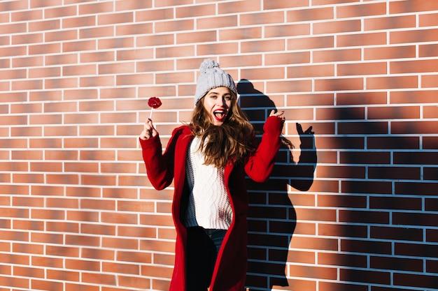 Ritratto bella ragazza in cappotto rosso con labbra lecca-lecca sul muro esterno. indossa un cappello lavorato a maglia, sembra soddisfatta.