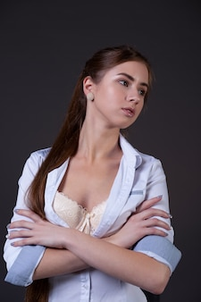 Portrait of a beautiful girl in sexy underwear and a light unbuttoned shirt