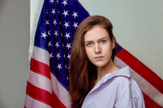 Portrait of beautiful girl in shirt on american flag background close up