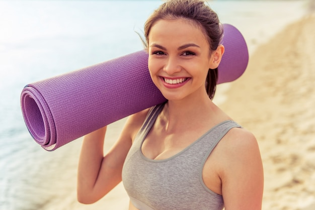 Portrait of beautiful girl in sport clothes holding a yoga mat.