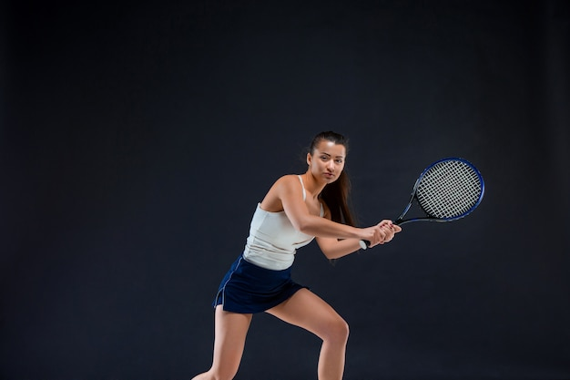 Portrait of beautiful girl tennis player with a racket on dark wall