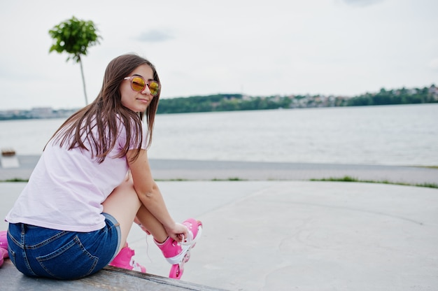 Portrait of a beautiful girl wearing sunglasses, t-shirt and shorts putting on rollerblades outdoor next to the lake.