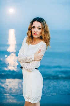 Portrait of a beautiful girl in a white dress on the beach