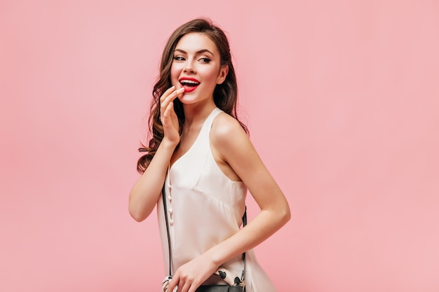 Portrait of beautiful girl in white dress touching her red lips. lady with handbag posing on pink background.