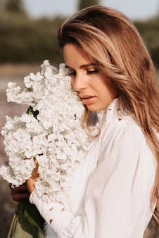 Portrait of a beautiful girl in a white dress with a bouquet of flowers in a field in summer Premium Photo