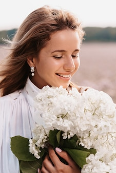 Portrait of a beautiful girl in a white dress with a bouquet of flowers in a field in summer