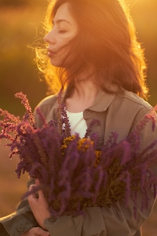 Portrait of a beautiful girl with a bouquet of lavender. sunset light and beautiful sensuality. the girl is enjoying the moment