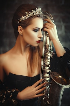 Portrait of a beautiful girl with a crown on her head and a saxophone in the hands is posing with jazz music. international jazz festival