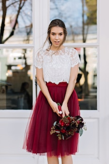 Portrait beautiful girl with light hairstyle in marsala tulle skirt on street. she holds bouquet of flowers and looking