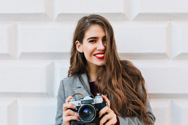 Portrait beautiful girl with long hair in grey coat on wall . she holds camera and looks happy.