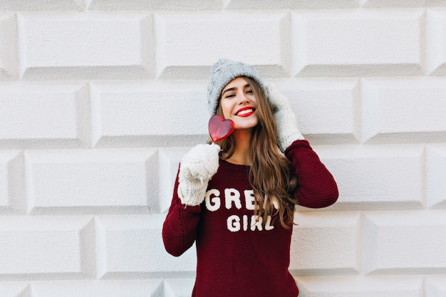 Bella ragazza del ritratto con capelli lunghi in maglione marsala e guanti bianchi sul muro grigio. tocca il cappello lavorato a maglia, tiene la caramella del cuore rosso e sorride.