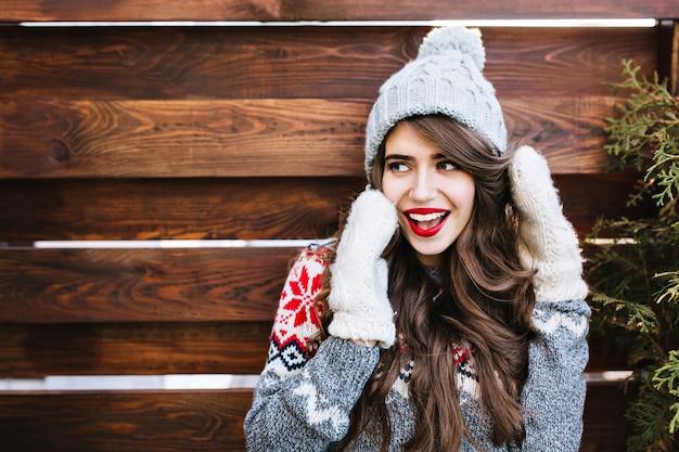 Bella ragazza del ritratto con capelli lunghi e labbra rosse in cappello lavorato a maglia e guanti caldi su legno. lei sorride di lato.