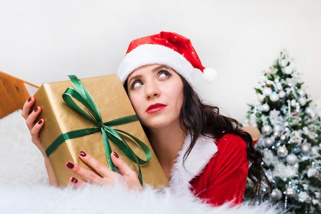 상자 현재와 크리스마스 모자와 긴 머리를 가진 세로 아름 다운 소녀. 사려깊은 얼굴 소녀. 좋은 크리스마스 선물을 꿈꾸십시오. 소녀는 생각합니다. 새해의 꿈과 희망.