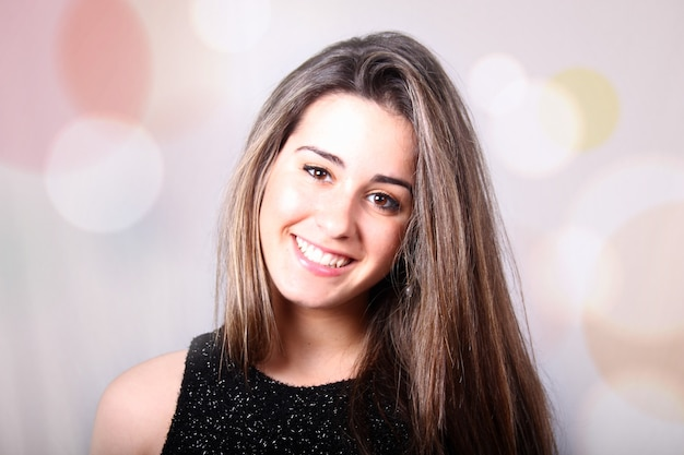 Portrait of a beautiful girl with long straight hair looking straight ahead with a smile