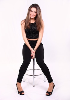 Portrait of a beautiful girl with long straight hair on a white background seated on a high stool