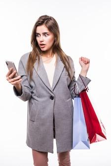 Ritratto di bella ragazza con il telefono cellulare e il sacchetto della spesa isolati su bianco