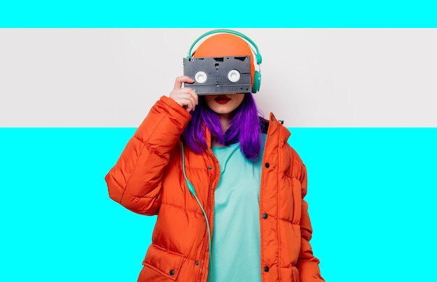 Portrait of a beautiful girl with purple hair in orange hat and jacket and with headphones and vhs cassette on white and blue background. trendy style