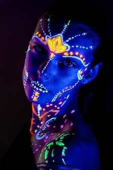 Portrait of beautiful girl with ultraviolet paint on her face
