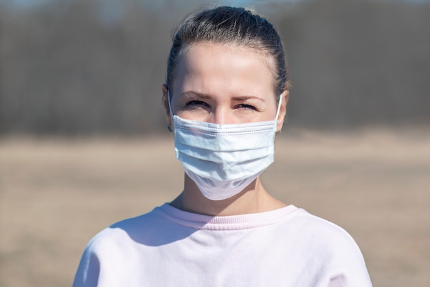 Portrait of beautiful girl, young person, woman in medical protective mask on face standing alone at empty street outdoors. coronavirus, pandemic, epidemic virus concept. covid-19, quarantine