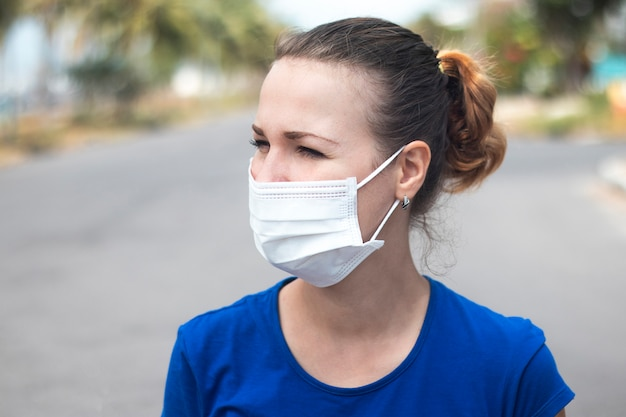 Portrait of beautiful girl, young person, woman in medical steril protective mask on face standing alone at empty street outdoors. coronavirus, pandemic, epidemic virus concept. covid-19, quarantine