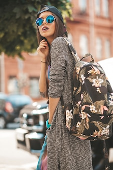 Portrait of beautiful glamor brunette teenager model in summer hipster clothes and bag. girl posing in the street. woman in round sunglasses and cap