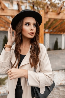 Portrait of a beautiful glamorous curly woman with a stylish hat in a fashionable beige coat with a fashion leather handbag in the city.  elegant feminine style and beauty