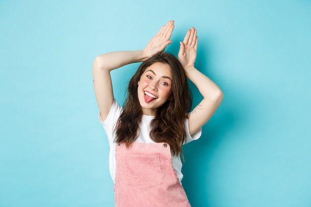 Portrait of beautiful glamour girl celebrating easter, showing bunny rabbit ears with hands above head, smiling joyful, standing over blue background.