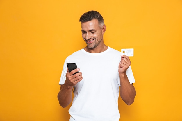 Portrait of beautiful guy 30s in white t-shirt holding mobile phone and credit card isolated on yellow