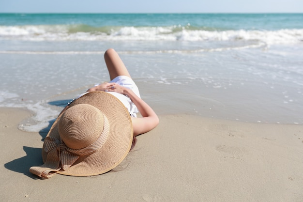 Portrait of beautiful and happiness woman enjoy holiday vacation and lying down on the beach
