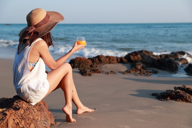Portrait of beautiful and happiness woman enjoy holiday vacation with orange juice on the beach