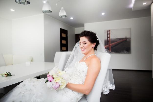 Portrait of beautiful happy bride sitting on sofa