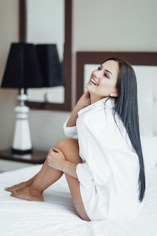 Portrait of a beautiful happy brunette girl sitting in bed and posing.