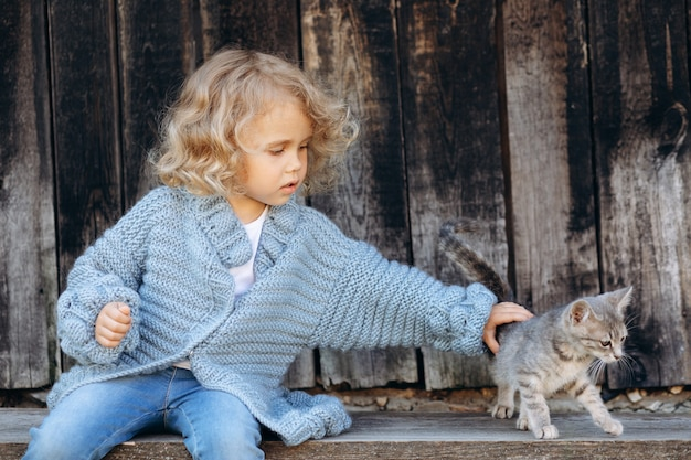 Portrait of a beautiful and happy curly girl in a blue knitted sweater playing with a kitten near a wooden wall