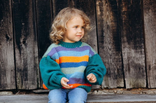 Portrait of a beautiful and happy curly girl in a knitted sweater near a wooden wall