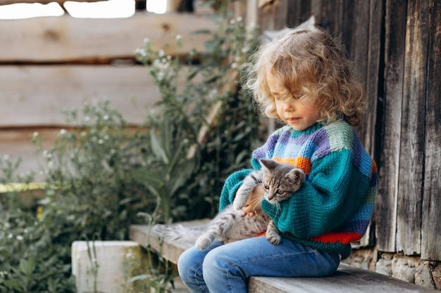 Portrait of a beautiful and happy curly girl in a knitted sweater playing with a kitten near a wooden wall