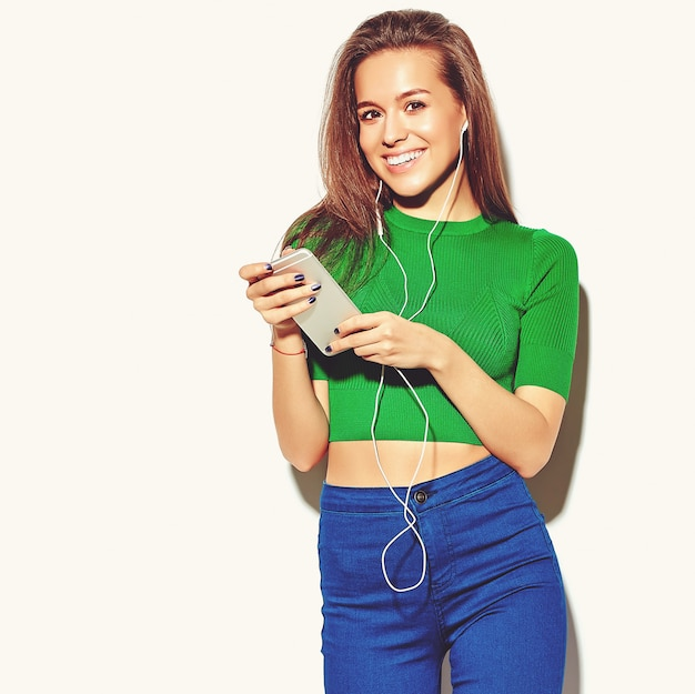 Ritratto di una bella ragazza felice carina donna bruna in abiti casual casual verde estate senza trucco isolato su bianco utilizzando uno smart phone