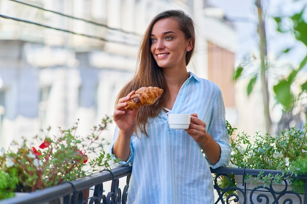 Portrait of a beautiful happy cute joyful smiling romantic woman with coffee cup and fresh baked croissant for french breakfast in the morning on a balcony