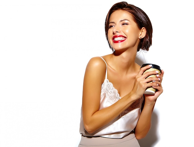 Portrait of beautiful happy cute sexy brunette woman with red lips in wide classic pants holding plastic coffee cup on white background